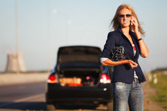 Fashion woman in sunglasses calling on phone next to broken car Royalty Free Stock Photography