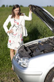 Woman and broken car. Woman watching the engine of a broken car Royalty Free Stock Photography