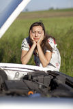 Woman and broken car. Woman watching the engine of a broken car Stock Image