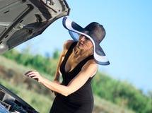 Woman with broken car. Woman with big hat near the broken car Stock Photos