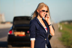 Fashion woman next to broken car calling on the phone Royalty Free Stock Photos