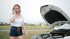 Woman and broken car calling for help on cell phone. broken car on the road. Young woman and broken car calling for help on cell phone stock footage