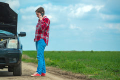 Woman with broken car on country road talking on mobile. Adult caucasian woman standing by the broken car on country road and talking on mobile phone Stock Photo