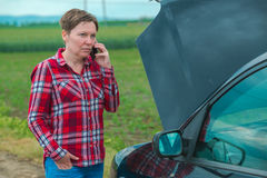 Woman with broken car on country road talking on mobile. Adult caucasian woman standing by the broken car on country road and talking on mobile phone Stock Image