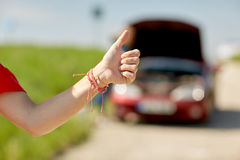 Woman with broken car hitching at countryside. Road trip, transport, travel, gesture and people concept - young woman with broken car showing thumbs up and Royalty Free Stock Photos