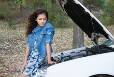 Woman with broken car inspecting engine Stock Photo