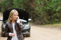 Woman at broken car with mobile phone Royalty Free Stock Images