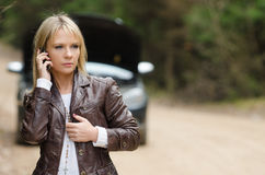 Woman at broken car with mobile phone Stock Image