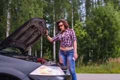Woman and broken car with opened hood.  Stock Images