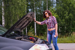 Woman and broken car with opened hood.  Royalty Free Stock Photos