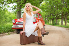Woman with broken car  sitting on suitcase. And waiting for help Stock Photography