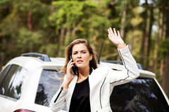 Woman with broken car talking through a phone Royalty Free Stock Photography
