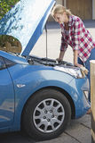 Woman With Broken Down Car Looking Under Bonnet Royalty Free Stock Photography