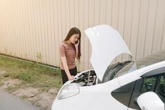 Woman and broken down car on street, Girl using mobile phone while looking problem in engine, Auto Concept stock image