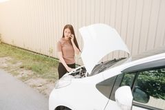 Woman and broken down car on street, Girl using mobile phone while looking problem in engine, Auto Concept stock photo