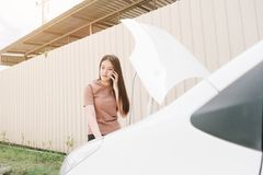 Woman and broken down car on street, Girl using mobile phone while looking problem in engine, Auto Concept royalty free stock images