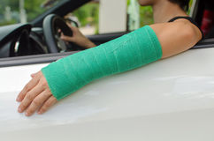Woman with broken hand in green cast sitting in car, insurance c Royalty Free Stock Images