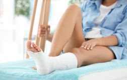 Woman with broken leg in cast. On couch Royalty Free Stock Photos