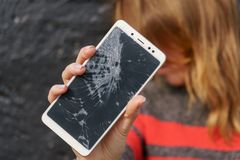 Woman with broken screen phone in his hand.  royalty free stock image