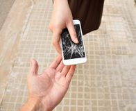 Broken screen phone. Woman with broken screen phone in his hand return it to its owner at the city street stock photo