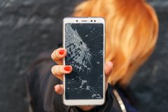 Woman with broken screen phone in his hand.  stock photos