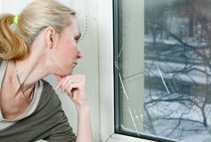 The woman at the broken window Royalty Free Stock Image