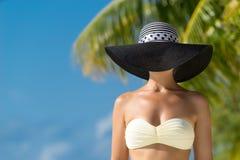 Woman with bronze tan enjoying beach relaxing joyful in summer by tropical blue water. Beautiful bikini model happy on travel wearing beach sun hat Royalty Free Stock Photos