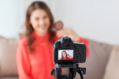 Woman with bronzer and camera recording video. Blogging, technology, videoblog, makeup and people concept - happy smiling woman or beauty blogger with bronzer Royalty Free Stock Photo