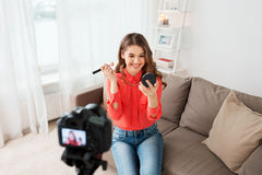 Woman with bronzer and camera recording video. Blogging, technology, videoblog and people concept - happy smiling woman or beauty blogger with bronzer, brush and stock photography
