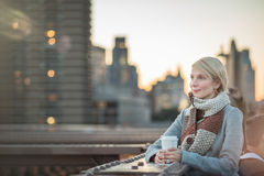 Woman on the Brooklyn Bridge Looking at Manhattan with a Coffee royalty free stock photography