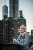 Woman on the Brooklyn Bridge Looking at Manhattan with a Coffee stock photos