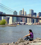 Woman in Brooklyn Bridge Park NYC USA. New York woman enjoys the view of Manhattan across the East River from Brooklyn Bridge Park stock image