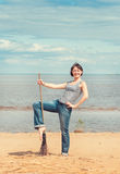Woman with broom on the beach Royalty Free Stock Photography