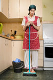 Woman with a Broom in the Kitchen Stock Images