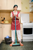 Woman with a Broom in the Kitchen Royalty Free Stock Photos