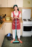 Woman with a Broom in the Kitchen Royalty Free Stock Image