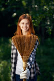 Woman with a broom, a woman doing cleaning in the garden, cleaning Royalty Free Stock Photo