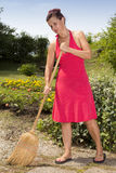 Woman brooming the garden path Royalty Free Stock Photography