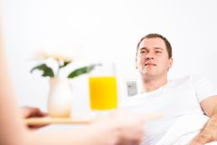Woman brought her boyfriend breakfast in bed Royalty Free Stock Image
