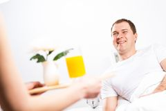 Woman brought her boyfriend breakfast in bed Stock Photography