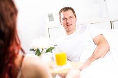 Woman brought her boyfriend breakfast in bed Stock Photos