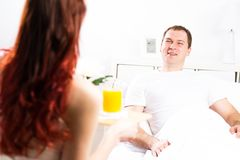 Woman brought her boyfriend breakfast in bed Royalty Free Stock Photo