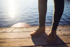 Woman in brown boots and green pants standing near water on wood background. Walking fashion hiking concept Stock Photo
