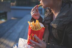 Woman in Brown Classic Trench Coat Eating Mcdo Fries during Daytime Stock Photo