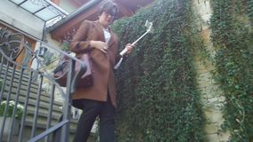 Woman down the stairs. A woman in a brown coat with a selfie stick and a phone goes down the stairs stock footage