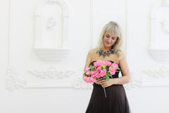 Woman in brown dress holds pink flowers Royalty Free Stock Photography