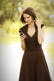Woman in brown dress with phone Royalty Free Stock Image