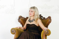 Woman in brown dress sits in vintage chair Royalty Free Stock Photography