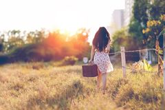 Woman in Brown Floral Dress Walking Near Fence Royalty Free Stock Photos
