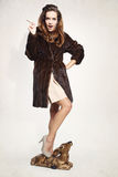 Woman in brown fur coat with fawn Royalty Free Stock Images